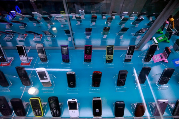 Mobile phones are seen in a shop window in Yangon